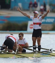 (R-L) Germany's Tim Grohmann, Lauritz Schoof and Phillipp Wende celebrate after winning the gold medal in the men's quadruple sculls final of the rowing event during the London 2012 Olympic Games, at Eton Dorney Rowing Centre in Eton, west of London, on August 3, 2012.   AFP PHOTO / DAMIEN MEYER