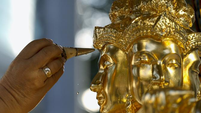 A priest sprinkles holy water at the repaired statue of Hindu god Brahma during a religious ceremony at the Erawan shrine in central Bangkok