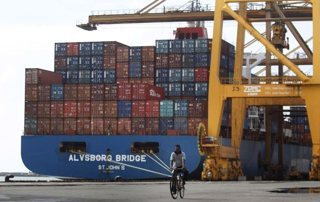 A dock worker  rides his bicycle past shipping containers at the main Sri Lankan port in Colombo