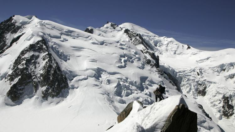 CORRECTS DATE OF AVALANCHE TO JULY 12, 2012  FILE - This June 1, 2005 file picture shows alpinists on the Arete Cosmique with a view of the north side of Mont Blanc du Tacul, left, the Mont Maudit, center, and the Mont Blanc, right. An avalanche in the French Alps on Thursday July 12, 2012 swept six climbers to their deaths, left at least nine injured and about a dozen others unaccounted for, authorities said. Rescuers are searching for the missing. (AP Photo/fls/Keystone/Arno Balzarini, File)
