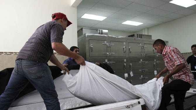 In this Aug. 31, 2012 photo, funeral parlor workers take away the body of a man whose murder authorities say is gang related at the morgue in San Salvador, El Salvador.  Six months after El Salvador brokered an historic truce between two rival gangs to curb the nation's daunting homicide rate, officials are split over whether the truce actually works. The gangs, which also operate in Guatemala and Honduras, are seeking truce talks in those countries as well. (AP Photo/Luis Romero)