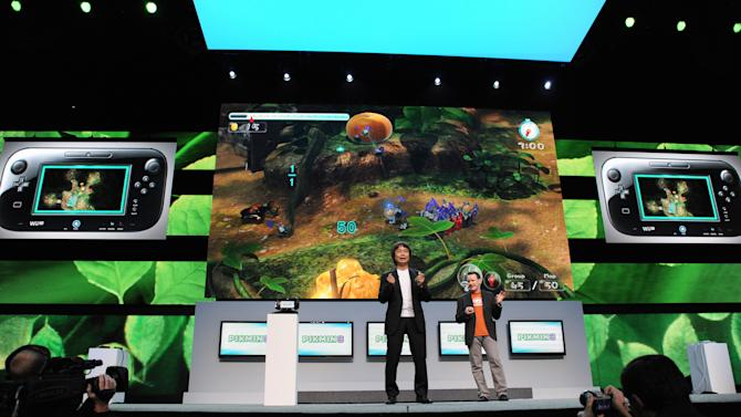 "COMMERCIAL IMAGE - In this photo provided by Nintendo of America, famed video game designer Shigeru Miyamoto, left, speaks on stage during the Nintendo All-Access Presentation @ E3 2012 in Los Angeles on June 5, 2012 (Vince Bucci/AP Images for Nintendo of America). Miyamoto demonstrates how the second screen of the Wii U GamePad controller is integrated into the new ""Pikmin 3"" game."