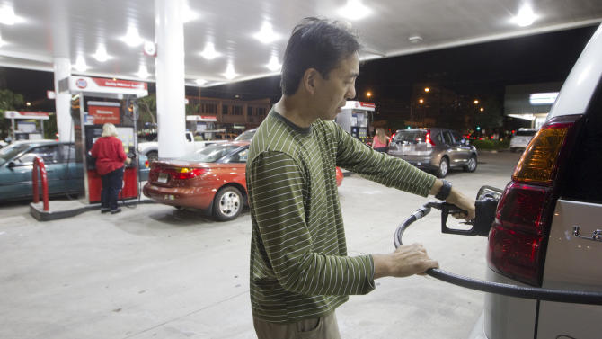 Lyndon Fong of Honolulu fills up his gas tank after learning of a tsunami waring Saturday, Oct. 27, 2012, in Honolulu. A tsunami warning has been issued for Hawaii after a 7.7-magnitude earthquake rocked an island off the west coast of Canada. The Pacific Tsunami Warning Center originally said there was no threat to the islands, but a warning was issued later Saturday and remains in effect until 7 p.m. Sunday. A small craft advisory is in effect until Sunday morning.(AP Photo/Eugene Tanner)