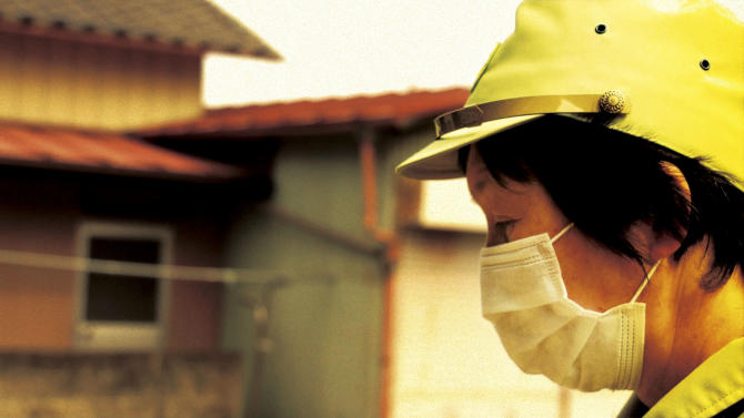"""In this image made from a scene from the film """"Fukushima: Memories of the Lost Landscape"""" released by Yojyu Matsubayashi, Kyoko Tanaka, a city council member of Minami Soma, patrols in the deserted town after evacuation of the residents, on April 3, 2011. Japanese film director Matsubayashi took a more standard documentary approach for his """"Fukushima: Memories of the Lost Landscape,"""" interviewing people who were displaced in the Fukushima town of Minami Soma. He followed them into temporary shelters in cluttered gymnasiums and accompanied their harried visits to abandoned homes with the gentle patience of a video-journalist. The March 2011 catastrophe in Japan has set off a flurry of independent films telling the stories of regular people who became overnight victims, stories the creators feel are being ignored by mainstream media and often silenced by the authorities. (AP Photo/Yojyu Matsubayashi) MANDATORY CREDIT, EDITORIAL USE ONLY"""