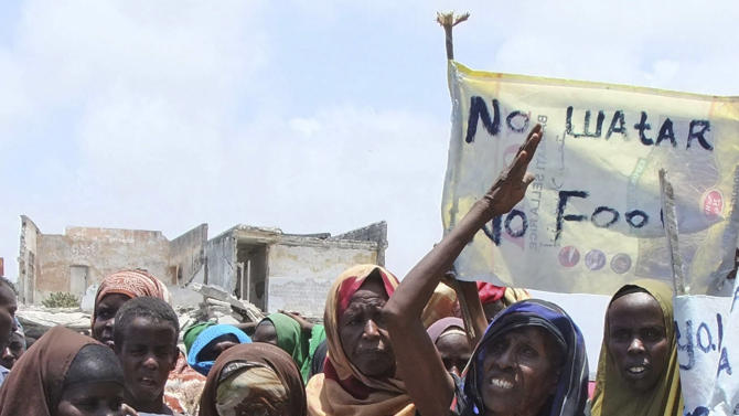 Somalis from southern Somalia demonstrate against the lack of food and water at Maka Al Mukarama road in Mogadishu, Somali, Wednesday, Sept. 14, 2011 carrying placards which read 'No water, No food'. A massive aid operation is currently underway to help millions of Somalis affected by the fighting and a famine caused by severe drought. (AP Photo/Farah Abdi Warsameh)