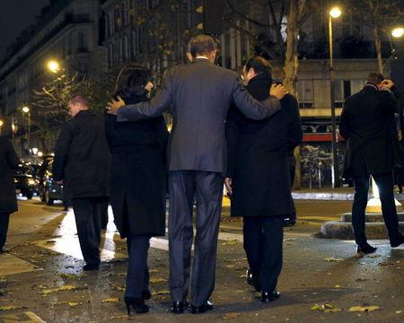 U.S. President Barack Obama, French President Francois Hollande (R) and Paris Mayor Anne Hidalgo (L) walk away after placing flowers at a makeshift memorial to pay tribute to the victims of the Paris attacks at the Bataclan in Paris