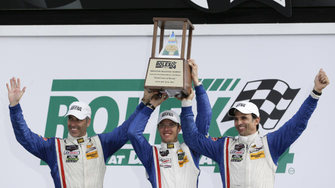 The Action Express team, from left, Joao Barbosa, of Portugal, Sebastien Bourdais, of France, and Christian Fittipaldi, of Brazil, celebrate with their trophy in Victory Lane after winning the IMSA Series Rolex 24 hour auto race at Daytona International Speedway in Daytona Beach, Fla., Sunday, Jan. 26, 2014.(AP Photo/John Raoux)