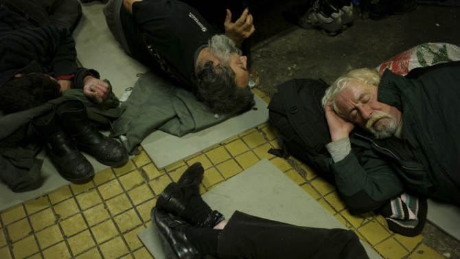In this photo taken early morning Friday, Jan. 11, 2013, homeless men sleep on the floor in a shelter called 'The Heated Street' in Budapest, Hungary. Hungary considers constitutional change to allow authorities to force homeless off the streets. (AP Photo/Bela Szandelszky)