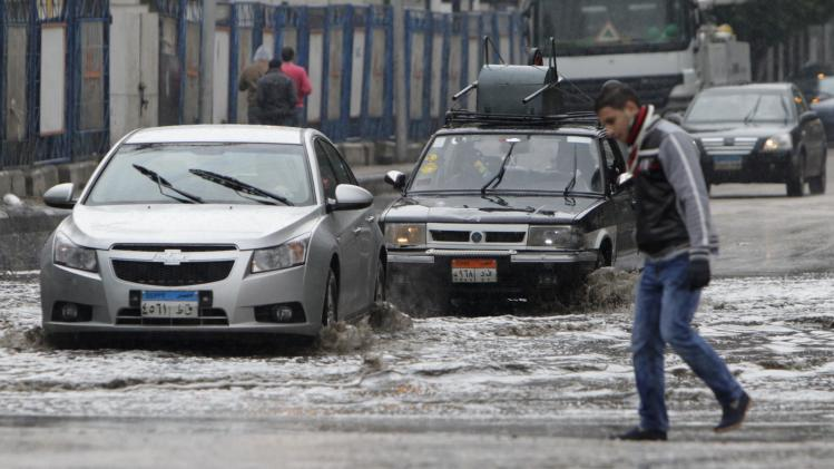Cars drive through a flooded street after a rainstorm in Cairo