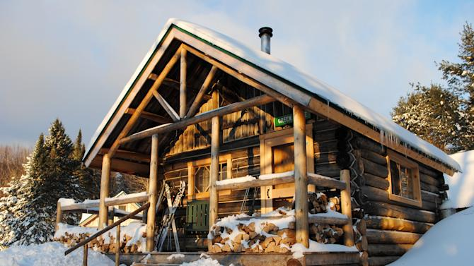 This December 2012 photo shows a rustic cabin in the snow at the Appalachian Mountain Club's Little Lyford Lodge and Cabins, a backcountry wilderness lodge near Greenville, Maine. In winter, visitors can reach the lodges and cabins only by cross-country skiing in.  (AP Photo/Lynn Dombek)