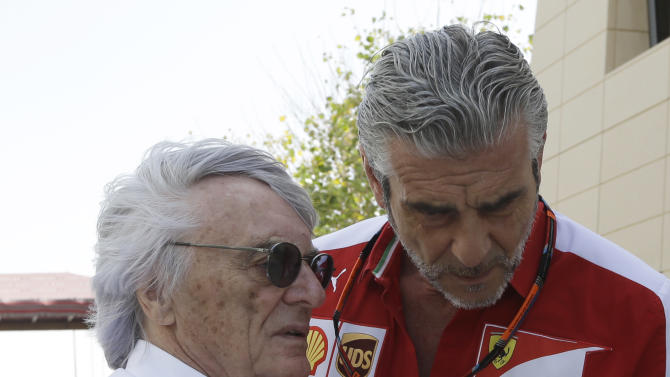 Chief executive of the Formula One Bernie Ecclestone, left, talks to Ferrari team principal Maurizio Arrivabene prior to the start of the Bahrain Formula One Grand Prix at the Formula One Bahrain International Circuit in Sakhir, Bahrain, Sunday, April 19, 2015. (AP Photo/Luca Bruno)