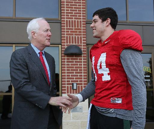 United States Sen. John Cornyn, left, shakes hands with Baylor quarterback Bryce Petty, right, before NCAA college football practice on Wednesday, Dec. 4, 2013, in Waco, Texas. Cornyn met with head fo