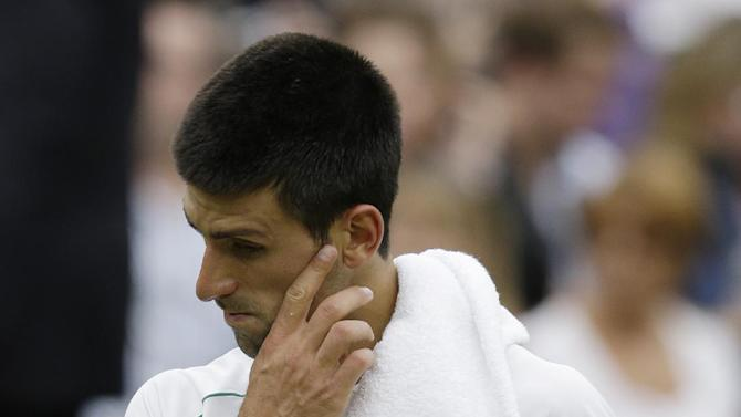 Novak Djokovic of Serbia reacts after his defeat to Roger Federer of Switzerland during a men's semifinals match at the All England Lawn Tennis Championships at Wimbledon, England, Friday, July 6, 2012. (AP Photo/Kirsty Wigglesworth)