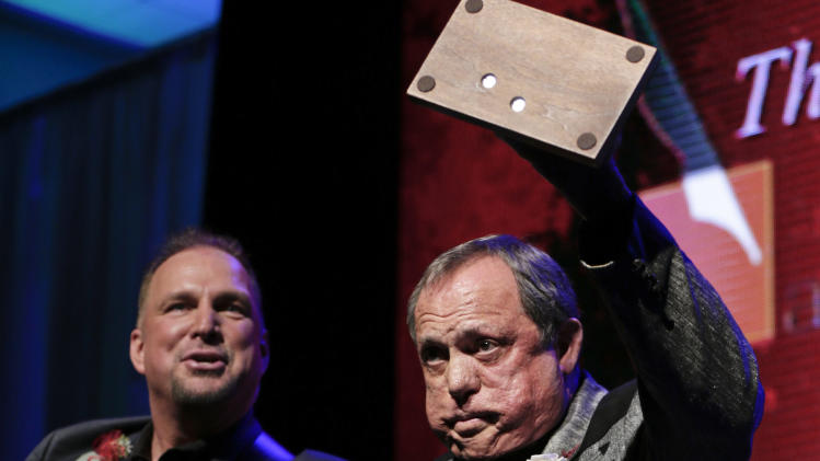 Kim Williams acknowledges the audience as he is inducted into the Nashville Songwriters Hall of Fame on Sunday, Oct. 7, 2012, in Nashville, Tenn. Garth Brooks watches at left. (AP Photo/Mark Humphrey)