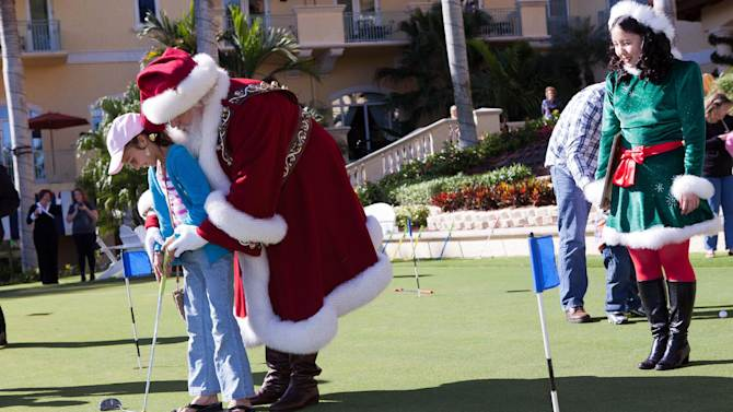 """Amber Shiver, 10, left, is taught how to use a putter by Santa Claus during the Macy's National Santa Tour at the The Ritz Carlton Golf Resort in Naples, Fla., Friday, Dec. 21, 2012. Santa made the stop at the resort to see ten Make-A-Wish children and their families as part of the Macy's national tour. Now in its fifth year, Macy's """"Believe campaign invites children to mail letter to Santa using Macy's Santa Mail letterboxes. Macy's donates a dollar for each letter mailed in store up to $1 million, to Make_A-Wish. (Erik Kellar/AP Images for Macy's)"""
