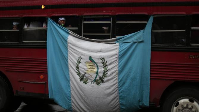A boy leans out the window of a bus with a Guatemalan national flag, in Guatemala City
