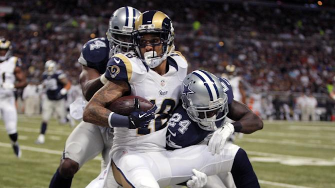St. Louis Rams wide receiver Austin Pettis (18) fights off Dallas Cowboys defenders Bruce Carter, left, and Morris Claiborne after catching a pass for an 11-yard gain during the first quarter of an NFL football game Sunday, Sept. 21, 2014, in St. Louis