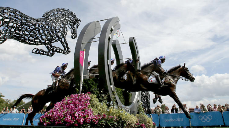 In this five frame multiple exposure, Lionel Guyon, of France, rides Nametis De Lalou as he competes in the equestrian eventing cross-country stage at the 2012 Summer Olympics, Monday, July 30, 2012, in London. (AP Photo/Charlie Riedel)