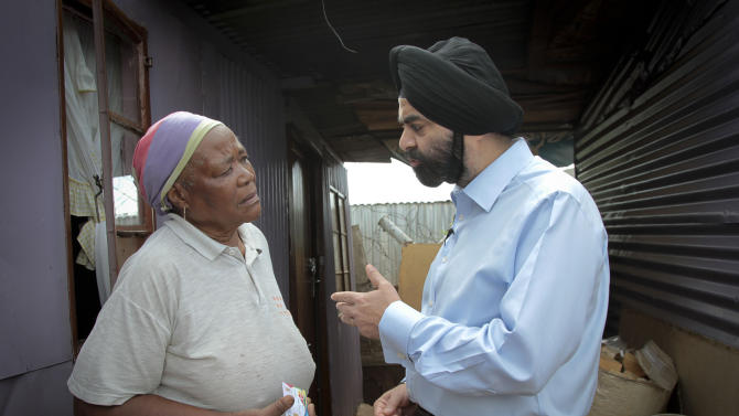 IMAGE DISTRIBUTED FOR MASTERCARD WORLDWIDE - Ajay Banga, MasterCard Worldwide President and CEO (right), discusses the benefits of the South African Social Security Agency (SASSA) Debit MasterCard card with Hilda Nkantini (left) at the Elias Motsoaledi settlement in Soweto outside Johannesburg on Wednesday Jan 16, 2013. Nkantini is one of the nearly six million South Africans who now receive their social grant payments securely and conveniently by using the Debit MasterCard card, which can also be used to pay for purchases, check balances and withdraw cash largely without incurring transaction fees. By the first half of 2013, an estimated 10 million South Africans - nearly one-fifth of the country's population – will be brought into the country's formal banking sector as a result of this card.  (Nadine Hutton/AP Images for MasterCard Worldwide)