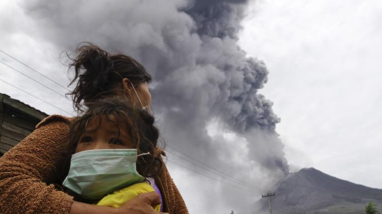 A mother holds her child as Mount Sinabung spews ash and hot lava during an eruption in Perteguhan village