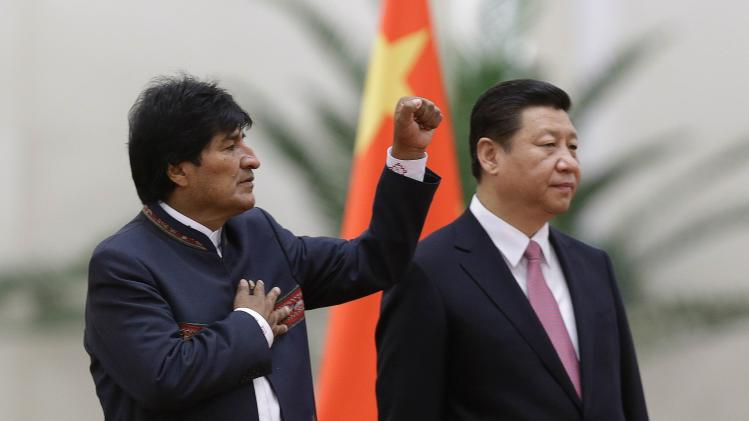 Bolivia's President Morales gestures while listening to the Bolivian national anthem with China's President Xi during a welcoming ceremony at the Great Hall of the People in Beijing