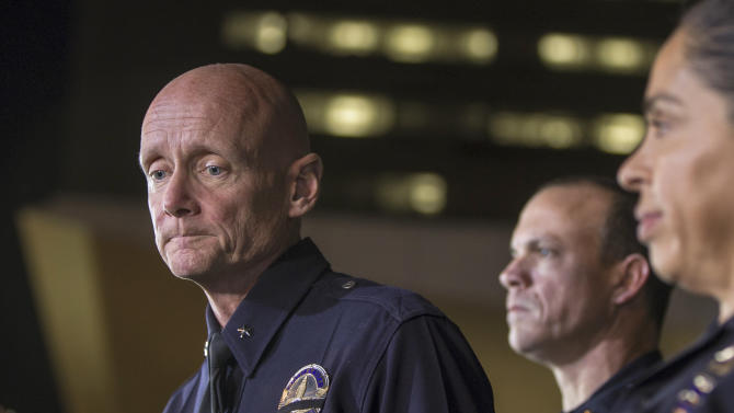 Los Angeles Police Commander Andrew Smith, left, expresses condolences for the death of a San Bernardino County deputy, as he briefs the media about the shootout scene in Big Bear that allegedly involves triple-murder suspect Christopher Jordan Dorner, during a late news conference in front of the Police Administration Building in Los Angeles, Tuesday, Feb. 12, 2013. Lt. Bill Whalen, of the Irvine Police Department, middle and LAPD officer Norma Eisenman, right, stand with Smith. (AP Photo/Damian Dovarganes)