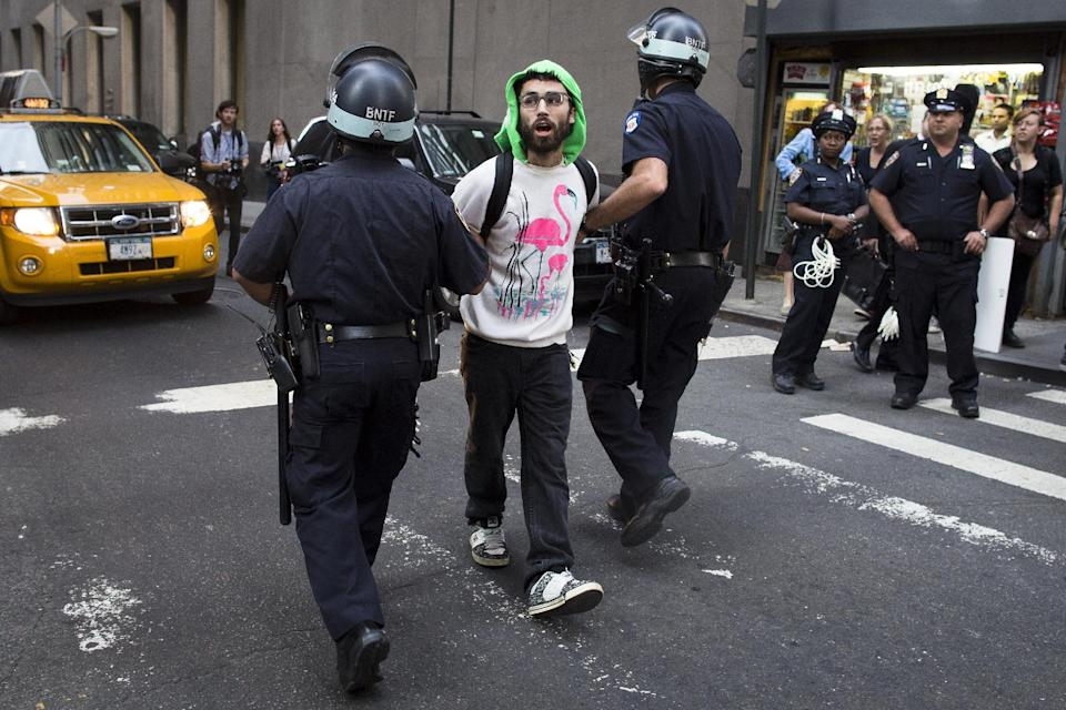 An Occupy Wall Street protestor is arrested on Wall Street for blocking pedestrian traffic on a sidewalk, Monday, Sept. 17, 2012, in New York. A handful of Occupy Wall Street protestors have been arrested during a march toward the New York Stock Exchange on the anniversary of the grass-roots movement. (AP Photo/John Minchillo)