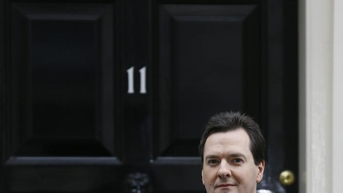 Britain's Chancellor George Osborne poses for the media with the traditional red dispatch box outside his official residence at No 11 Downing Street in London, as he departs to deliver his annual budget speech to the House of Commons, Wednesday, March 20, 2013. (AP Photo/Kirsty Wigglesworth)