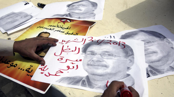 A Palestinian writes the name of Maysara Abu Hamdiyeh, over his portrait  during a protest in the West Bank city of Jenin, Tuesday, April 2, 2013. Abu Hamdiyeh, 64, who was serving a life sentence for attempted murder, died of cancer in Israeli jail. (AP Photo/Mohammed Ballas)