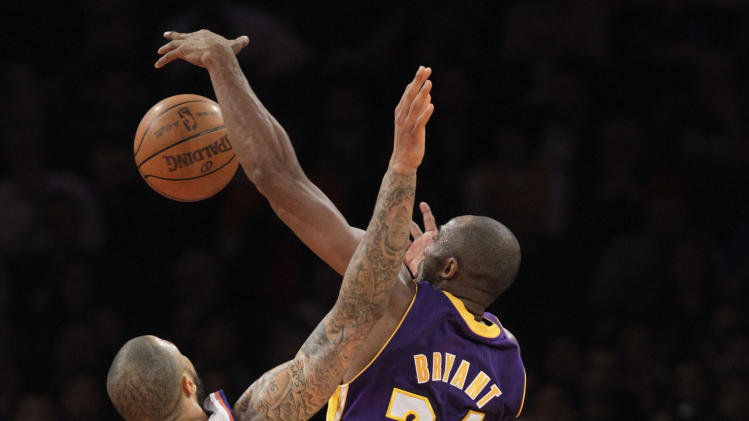 Los Angeles Lakers guard Kobe Bryant (24) grabs a rebound in front of New York Knicks center Tyson Chandler (6) in the second half of their NBA basketball game at Madison Square Garden in New York, Thursday, Dec. 13, 2012.  (AP Photo/Kathy Willens)