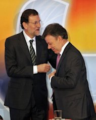 Spain's Prime Minister Mariano Rajoy (L) is greeted by Colombia's President Juan Manuel Santos during the inauguration of a Spain-Colombia economic forum at the Chamber of Commerce in Bogota, Colombia