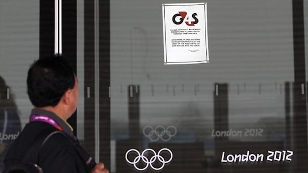 A visitor to the Olympic Park reads a 4GS notice stuck to a window at the Aquatics centre, in the Olympic Park (Reuters)
