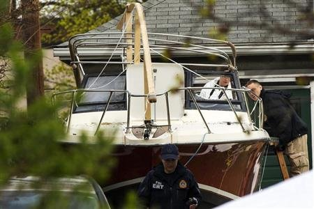 Members of the FBI Evidence Recovery Team inspect the boat where Boston Marathon bombing suspect Dzhokhar Tsarnaev was hiding at 67 Franklin St. in Watertown, Massachusetts, April 20, 2013. REUTERS/Lucas Jackson