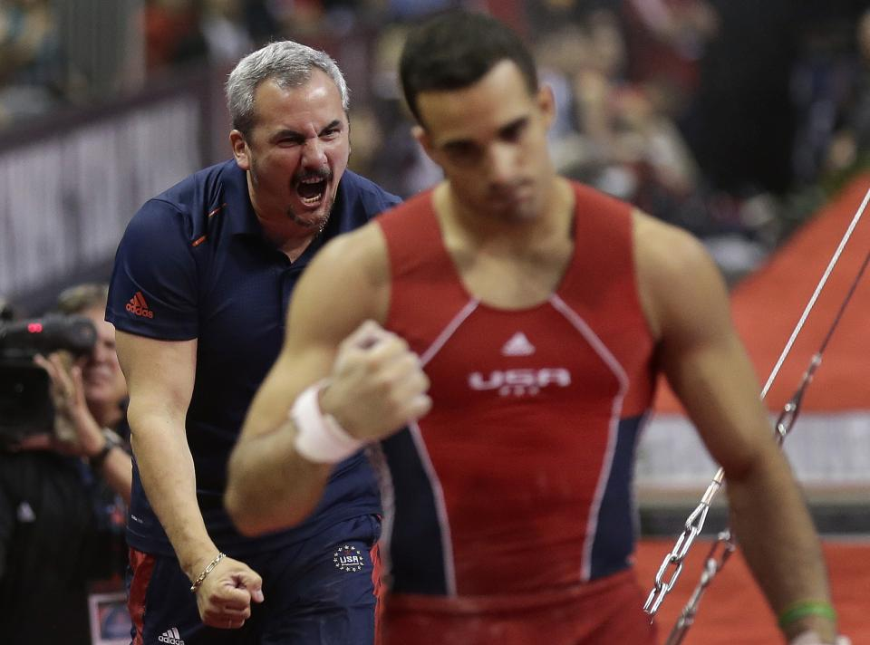 Coach Yin Alvarez, left, reacts after his step son, Danell Leyva's performance on the horizontal bar during the final round of the men's Olympic gymnastics trials, Saturday, June 30, 2012, in San Jose, Calif. (AP Photo/Gregory Bull)