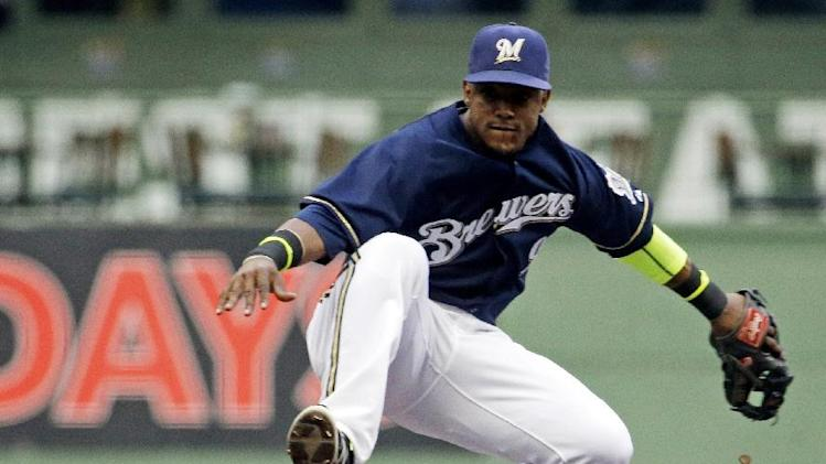 10ThingstoSeeSports - Milwaukee Brewers shortstop Jean Segura leaps over Cincinnati Reds' Skip Schumaker to turn a double play on a ball hit by Todd Frazier during the first inning of a baseball game Monday, July 21, 2014, in Milwaukee. (AP Photo/Morry Gash, File)