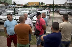 People gather outside a government-run car dealership …