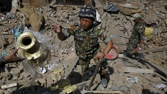 Nepalese army personnel recover goods from a collapsed house after Saturday's earthquake in Bhaktapur, Nepal