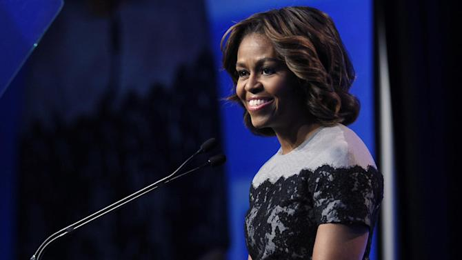 FILE - In this March 14, 2014 file photo, first lady Michelle Obama speaks in Washington. When Michelle Obama arrives in China later this week, she will stress the message that she's carried on past trips outside the U.S. It's about the importance of education for young people around the world, and the role Mrs. Obama says education played in helping her get ahead in her own life. She departs Wednesday on her third solo international trip as first lady. The weeklong journey to China includes stops in Beijing and two other cities where she is to meet with school and university students, as well as tour some of China's historic cultural sites. (AP Photo/Susan Walsh, File)