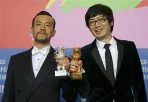 Actor Liao Fan and director Diao Yinan pose with Silver Bear for Best Actor and Golden Bear for Best film after awards ceremony of 64th Berlinale International Film Festival in Berlin