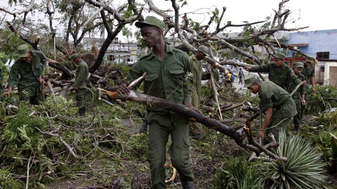 Soldiers removes trees that fell during the passing of Hurricane Sandy in Santiago de Cuba, Cuba, Friday Oct. 26, 2012. Sandy was a Category 2 hurricane when it wreaked havoc in Cuba on Thursday, killing 11 people in eastern Santiago and Guantanamo provinces as its winds and rain destroyed thousands of houses and ripped off roofs.  (AP Photo/Franklin Reyes)