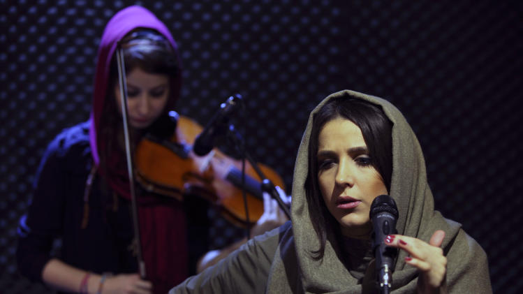 "In this picture taken on Friday, Jan. 25, 2013, female Iranian back vocalist Azadeh Ettehad and violinist Nastaran Ghaffari, both members of a band called ""Accolade,"" perform in an unauthorized stage performance in Tehran, Iran. Headphone-wearing disc jockeys mixing beats. It's an underground music scene that is flourishing in Iran, despite government restrictions. (AP Photo/Vahid Salemi)"