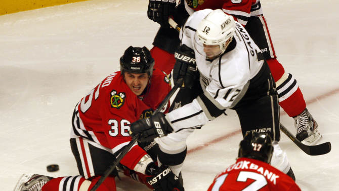 Los Angles Kings' Simon Gagne (12) gets off a shot over Chicago Blackhawks' Dave Bolland (36) in the second period of an NHL hockey game on Sunday, Feb. 17, 2013, in Chicago. The Blackhawks won 3-2. (AP Photo/John Smierciak)