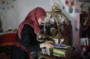 Isra Al-Modallal, a spokeswoman of the Hamas government in Gaza, prepares herself before heading to the office, at her house in Rafah refugee camp