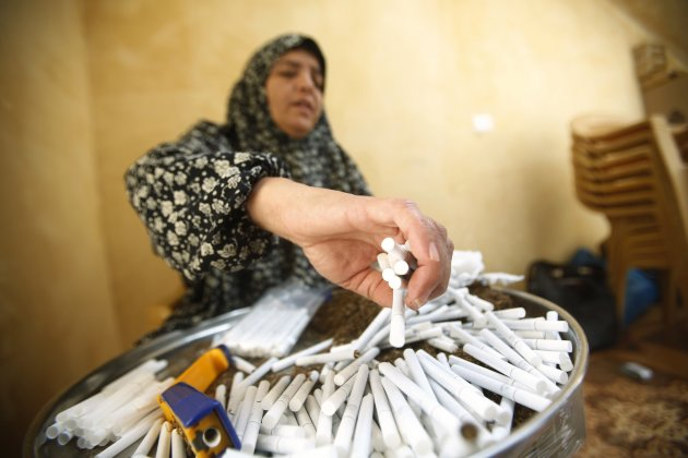 A Palestinian woman arranges hand-rolled cigarettes for sale in village near Jenin