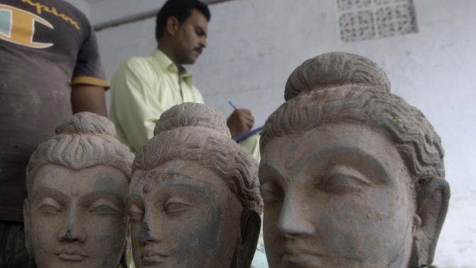 In this Friday, July 6, 2012 photo, A Pakistani journalist takes notes next to ancient Buddhist sculptures seized by police Friday, that smugglers were attempting to spirit out of the country, in Karachi, Pakistan. Pakistani officials say police have seized many sculptures of Buddha and other related religious figures worth millions of dollars that experts indicated could be over 2,000 years old. (AP Photo/Shakil Adil)