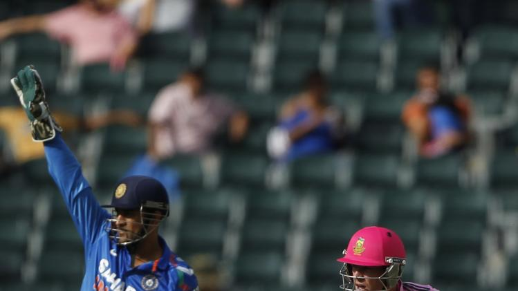 South Africa's captain de Villiers makes a run as India's captain and wicketkeeper Dhoni looks on during their first ODI in Johannesburg
