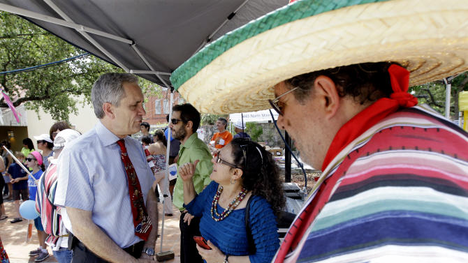 In this May 5, 2012 photo, U.S. Rep. Lloyd Doggett, D-Texas, left, visits with people during a stop at an art fair, in San Antonio. The soaring Hispanic population in Texas may not help Hispanic congressional hopefuls in the state's primary elections Tuesday, May 29, 2012. Two of the new districts are predominately Hispanic. But the front-runner in one is Doggett, a nine-term representative, who is white, while Hispanic candidates in the other face a strong opponent in state lawmaker Mark Veasey, who is black. (AP Photo/Eric Gay)