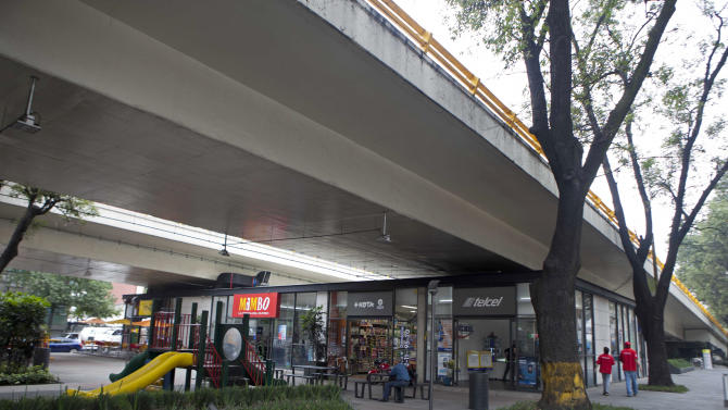 In this photo taken on Sept. 27, 2012, a man walks under a popular bridge where the city made way for a taco joint and playground, near the hip neighborhood of Condesa, in Mexico City. The government is trying to transform one of the world's largest cities by beautifying public spaces, parks and monuments buried beneath a sea of honking cars, street hawkers, billboards and grime following decades of dizzying urban growth. (AP Photo/Eduardo Verdugo)