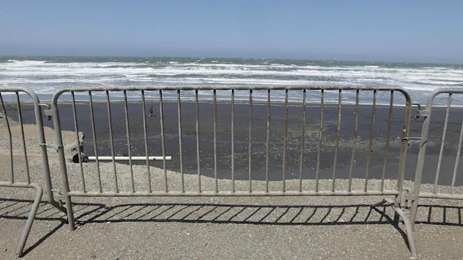 In this photo from Thursday, May 24, 2012, barricades stand at the parking lot at Ocean Beach in San Francisco. In San Francisco, officials are mulling a significant retreat on its western flank, where the Great Highway is under assault from the Pacific Ocean. Right now, a beach parking lot that abuts the highway is crumbing into the sea just across the highway from the San Francisco Zoo. (AP Photo/Jeff Chiu)
