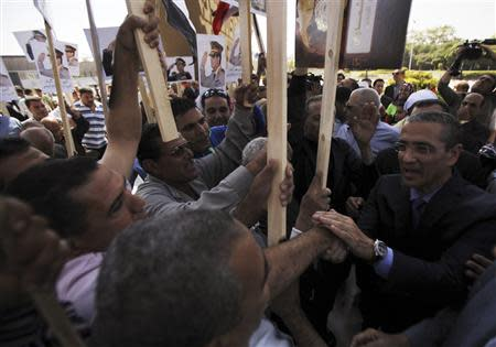 The son of late President Anwar Sadat shakes hands with people and supporters of the army at his father's tomb in Cairo